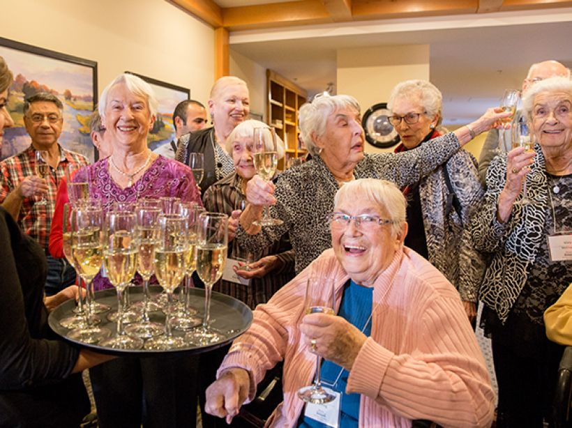 A group of senior residents gathered for a celebration toast of champagne at Origin at Spring Creek