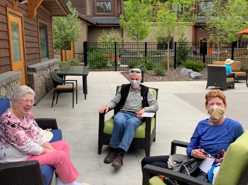 Courtyard at Origin at Spring Creek, with a young boy, a senior woman, and a senior man sitting on patio chairs, wearing face masks, looking at the camera