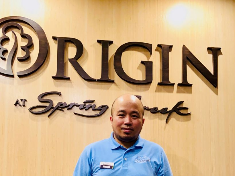 Louie standing in front of an Origin at Spring Creek sign