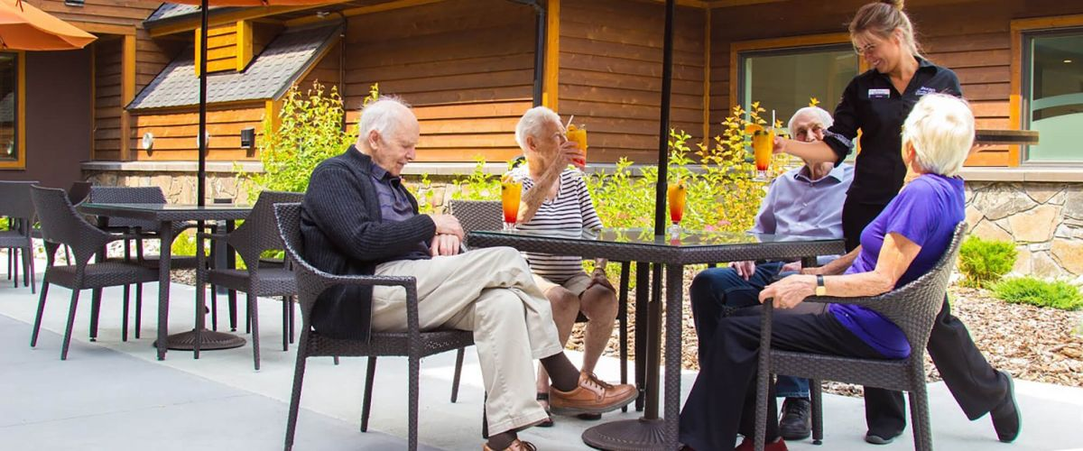 Three seniors sit on a patio at the Mineshaft Tavern at Origin at Spring Creek in Canmore, Alberta