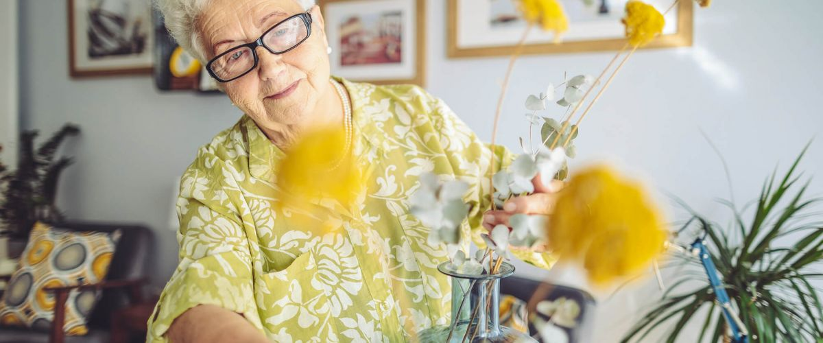 Senior woman wearing glasses arranges yellow flowers in a vase