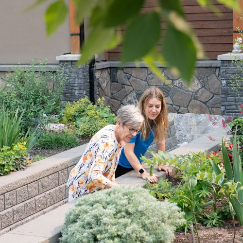 A female senior resident at Origin at Spring Creek and a Life Enrichment Coordinator in a blue uniform look at flowers and greenery in a garden space at Spring Creek