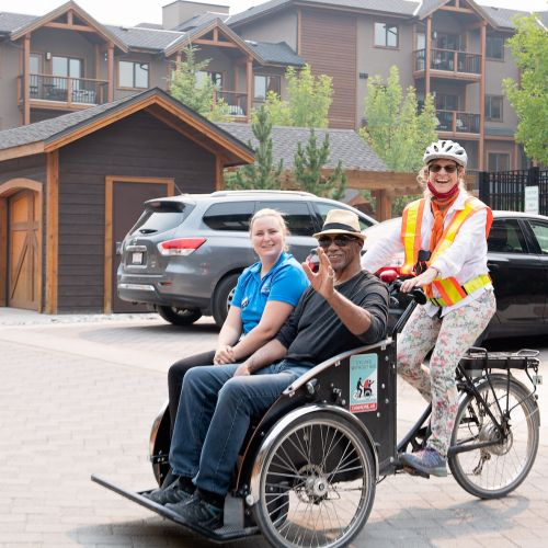 A senior resident and an Origin companion sit on a two-man bicycle driven by a woman wearing a helmet.