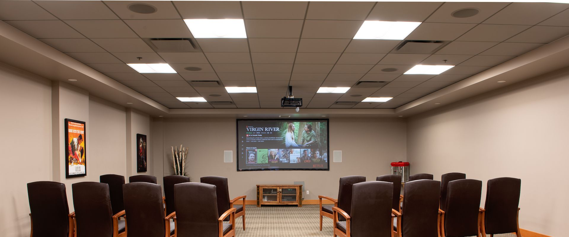 A spacious theatre and media room in the Origin at Spring Creek facility, with grey walls decorated, a grey patterned carpet, a large screen and projector, and two rows on either side of the room with comfortable leather chairs facing the screen.
