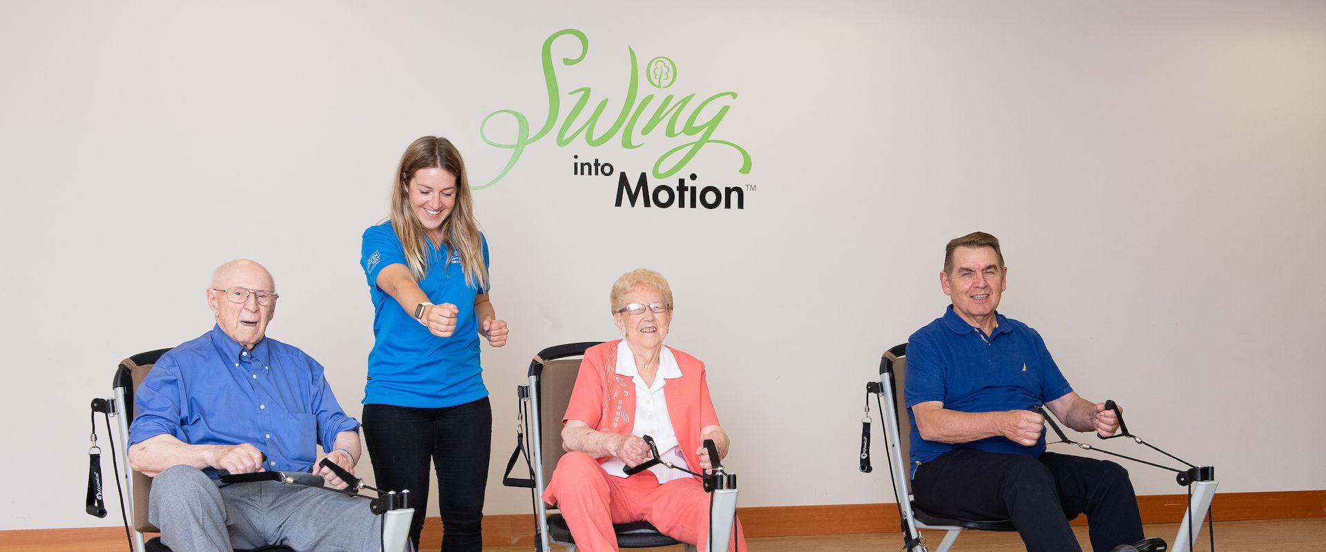 A smiling female Life Enrichment Coordinator at Origin demonstrates to three senior residents how to use an adaptive bicycle exercise machine as the three members use their personal exercise machine in the facility's gym.