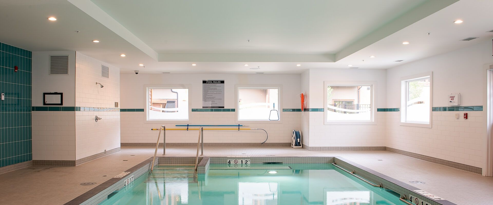 A bright blue indoor pool with bright lighting, white and turquoise tiles and sunlit windows.