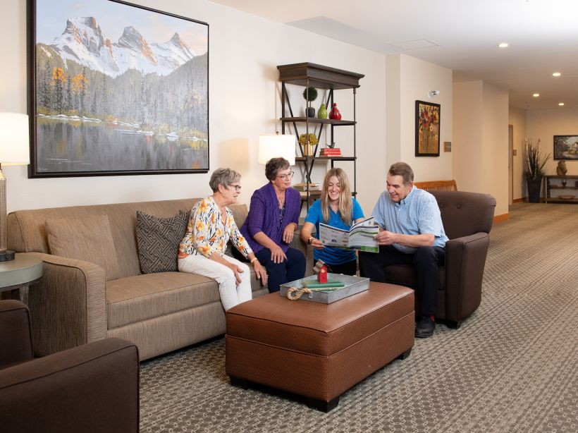Three senior residents and a younger adult companion chat in a comfortable living space at Origin at Spring Creek.