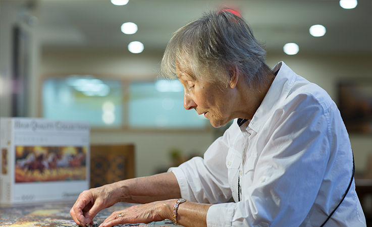 Side profile of a senior resident at Origin at Spring Creek working a table on a puzzle