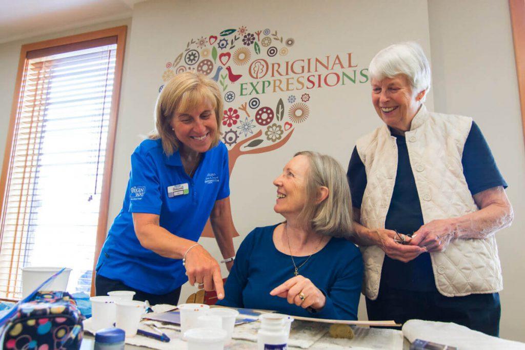 Origin at Spring Creek staff member looks at artwork with two senior residents at Origin at Spring Creek.