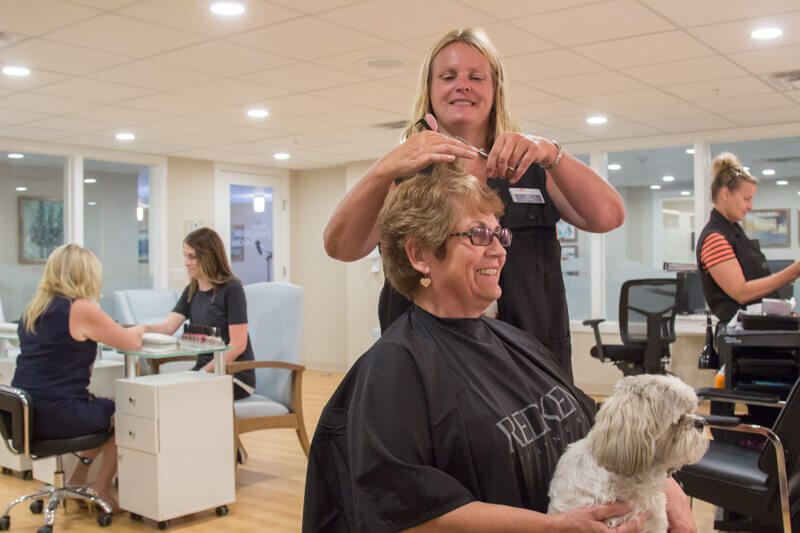 Senior woman with dog in her lap gets a haircut at the Evergreen Spa at Origin at Spring Creek