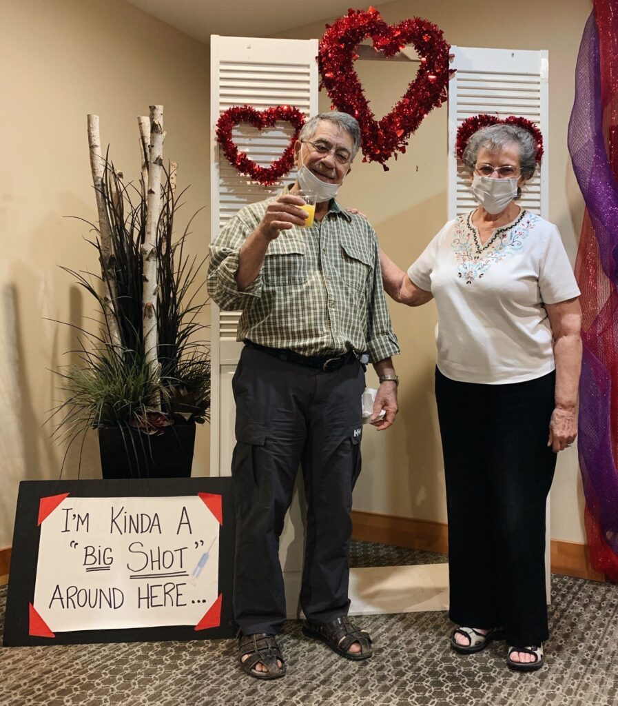 """Senior couple (male and female) wearing face masks in front of a sign that says """"I'm Kinda A 'Big Shot' Around Here"""""""