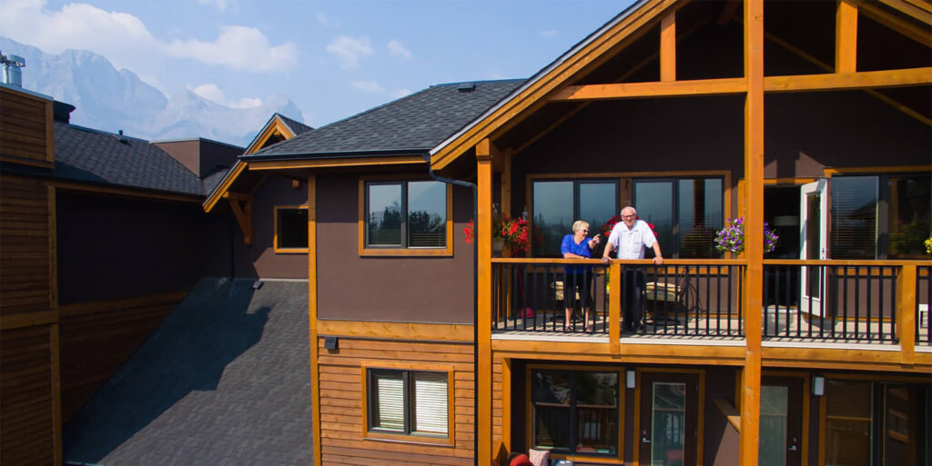 Two seniors stand on the balcony of a suite at Origin at Spring Creek
