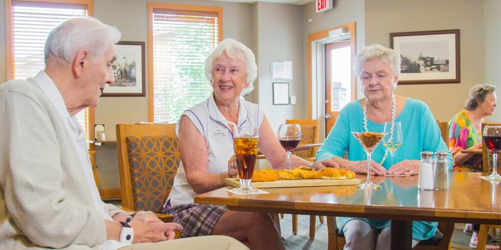 Three seniors sitting at a table at the Mineshaft Tavern in Canmore, Alberta, enjoying wine and cocktails