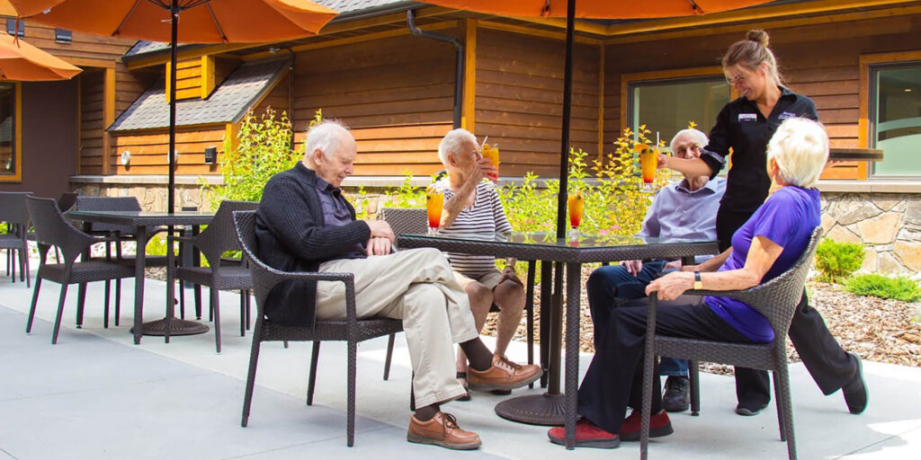 Four seniors site on a patio with drinks at the Mineshaft Tavern at Origin at Spring Creek in Canmore, Alberta.