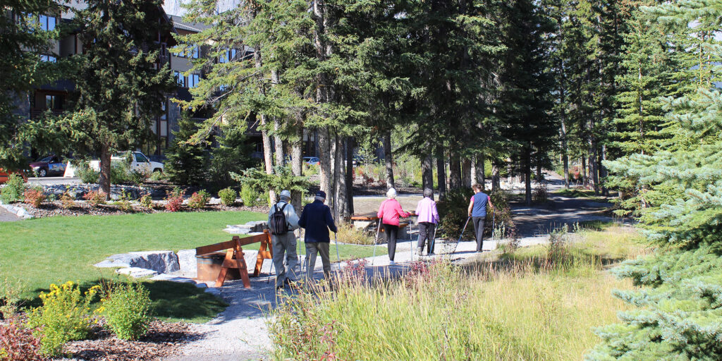 Four seniors and a staff guide walk on a trail path near Origin at Spring Creek in Canmore, Alberta