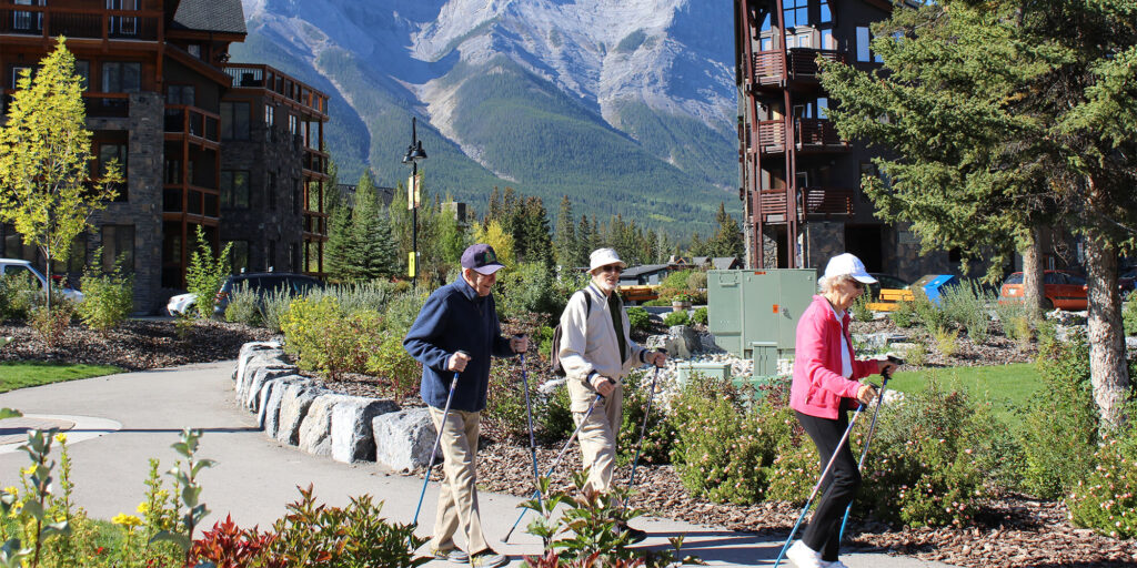 Three seniors with walking sticks on a walking path at Spring Creek in Canmore, Alberta