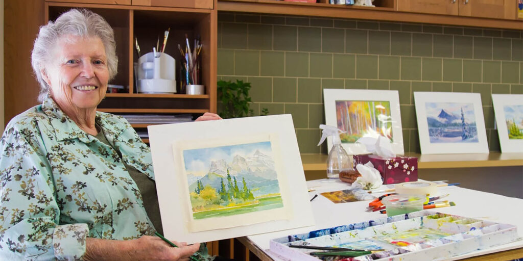 A female resident at Origin at Spring Creek holds up a painting she made in the Arts & Crafts room.