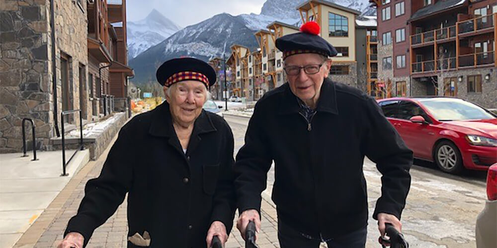 A senior woman and man walk down the street in Spring Creek Mountain Village in Canmore, Alberta, with the mountains in the background.