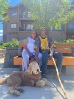 The couple, Jane and Richard, are sitting on a bench smiling towards the camera. They are outside of the buildings. There is also a dog lying beside them.
