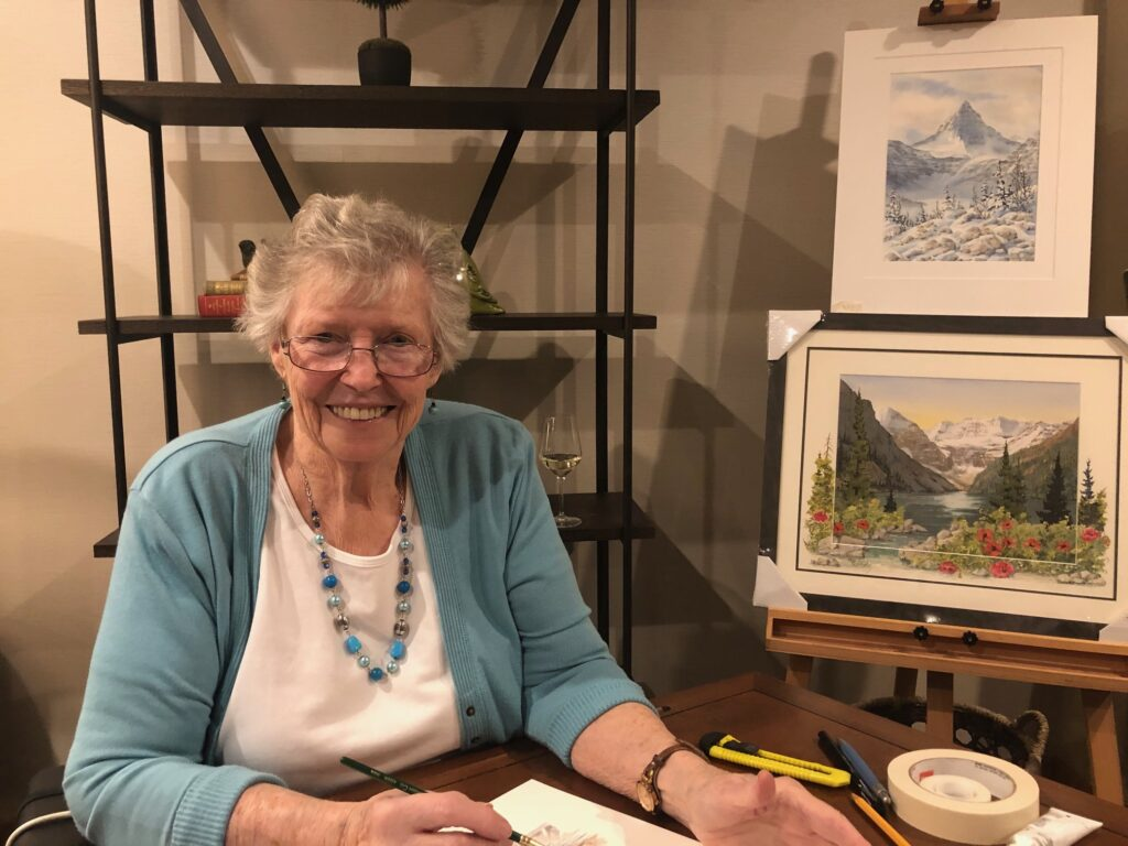 Marilyn Kinsella, artist and Origin resident, sits at a desk painting with an easel in the background with two of her artworks displayed
