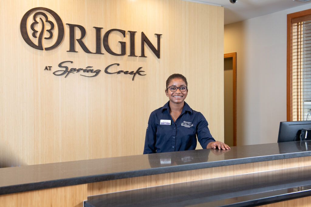 A female Origin at Spring Creek front desk team member standing behind the front desk at Origin at Spring Creek, smiling and welcoming you to the facility.