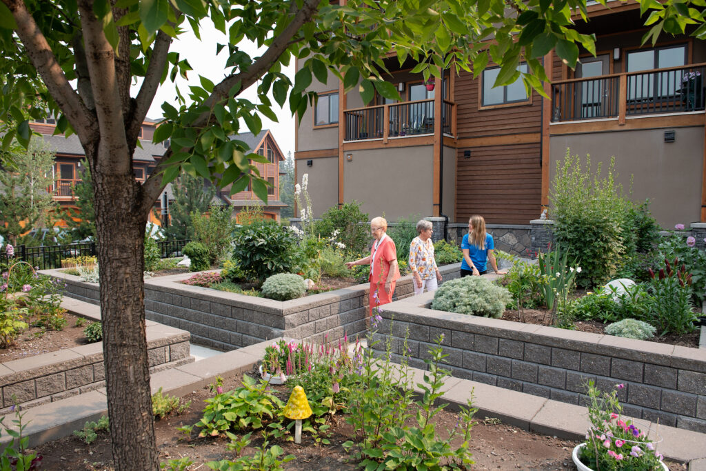 Two female senior residents and a female Life Enrichment Coordinator walk beside the brick-lined garden beds together, looking at the foliage, lush flowers and a large tree nearby.