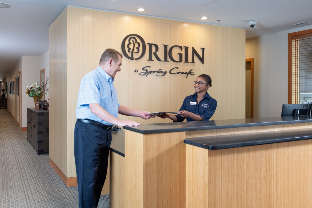 A smiling female staff member in a black uniform hands a male senior resident a form at the Origin at Spring Creek front desk.
