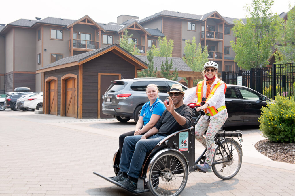Two seniors sit on a two-man bicycle driven by a woman wearing a helmet