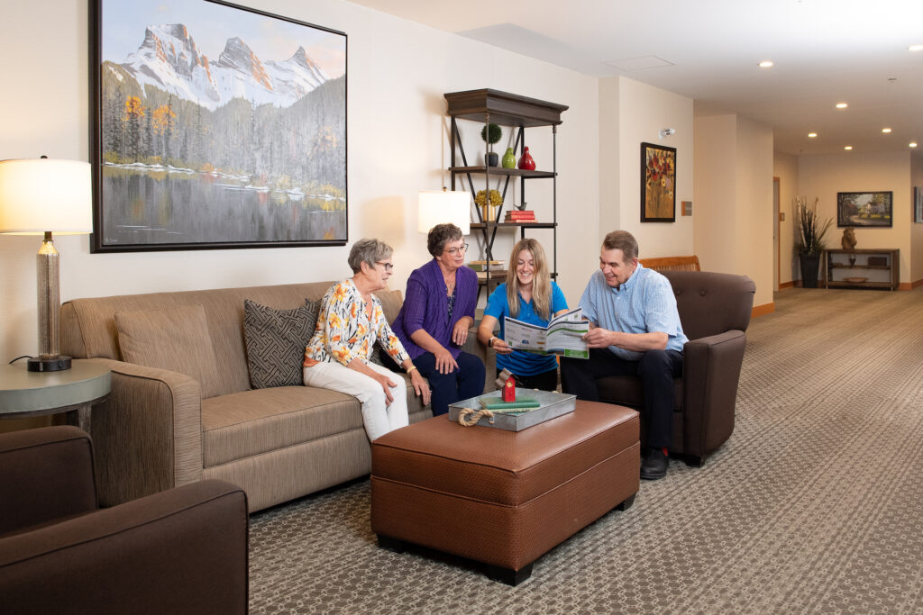 Three senior residents and a younger Origin staff member chat in a comfortable living space at Origin at Spring Creek