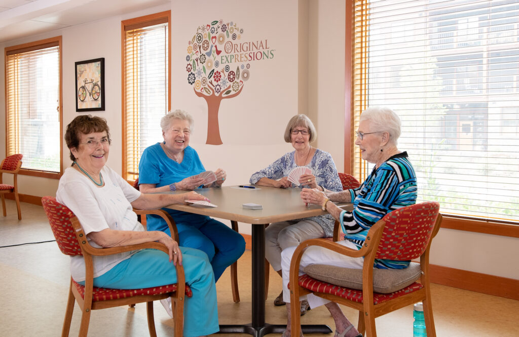 Four smiling female senior residents all dressed in blue and white enjoy a game of cards as they sit at a table in front of a bright, sunlit window.